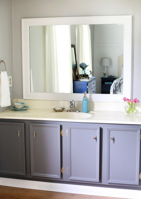 Frame in your bathroom mirror! It looks way better than a plain, builder grade mirror, and it's easier than you think! Click through to the post for the tutorial!