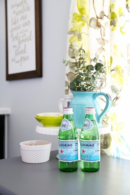 Small aqua pitcher with eucalyptus, Pellegrino. Beautiful white IKEA SEKTION GRIMSLOV kitchen with aqua and green accents, a gorgeous marble hexagon backsplash, and quartz countertops. | JustAGirlAndHerBlog.com