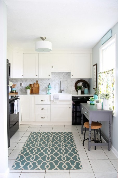 Beautiful white IKEA SEKTION GRIMSLOV kitchen with aqua and green accents, a gorgeous marble hexagon backsplash, and quartz countertops. | JustAGirlAndHerBlog.com