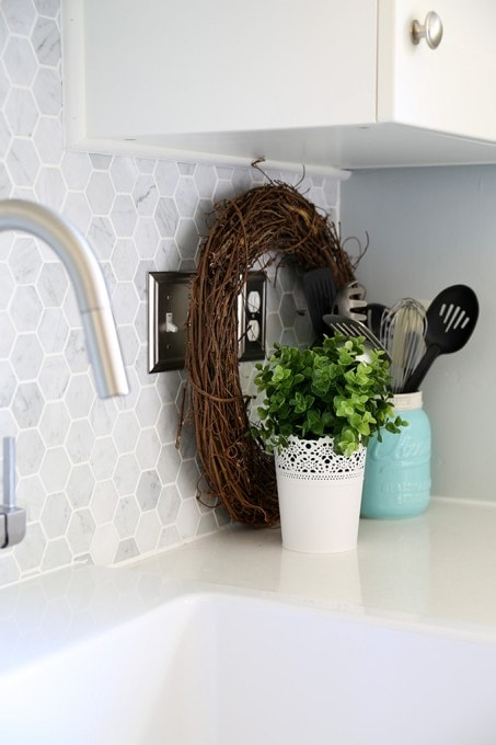 Wild Grapevine Wreath. Beautiful white IKEA SEKTION GRIMSLOV kitchen with aqua and green accents, a gorgeous marble hexagon backsplash, and quartz countertops. | JustAGirlAndHerBlog.com