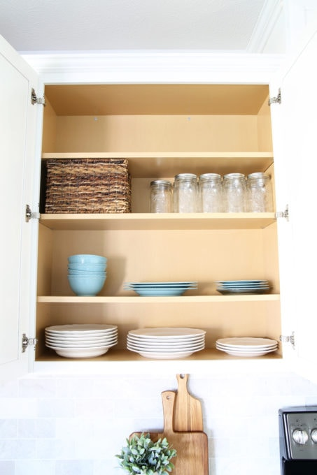 Organized Kitchen Cabinet, Using a Wicker Storage Basket to Hold Extra Utensils that Are Needed but Not Used Often