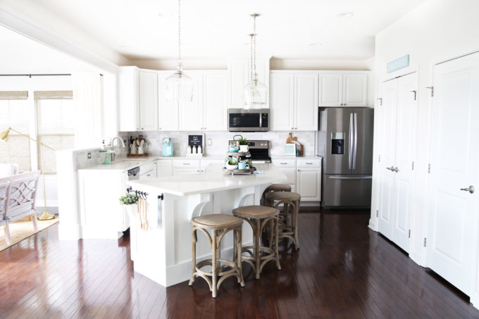 White Kitchen with Clear Pendant Lights Over the Island