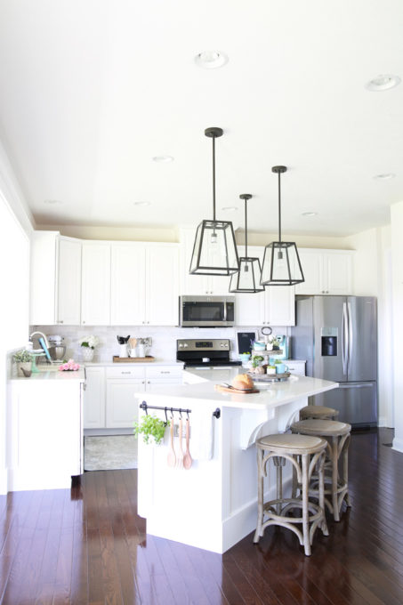 Home- A gorgeous white kitchen makeover with dark hardwood floors, quartz countertops in Caesarstone London Grey, marble subway tile backsplash, farmhouse pendant lights, weathered wood accents, and craftsman style trim work. They took a generic Ryan Homes Palermo kitchen and customized it beautifully.