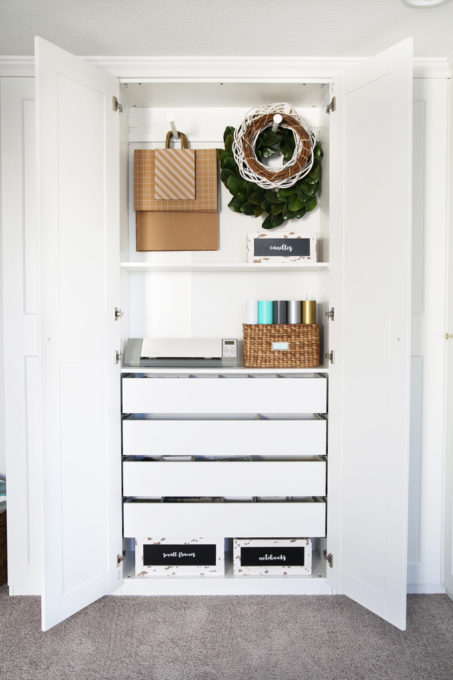 The IKEA PAX system was the perfect way to organize this messy corner of my office. I was able to store so much in the cabinets! | organized home office, office organization, IKEA hack, PAX wardrobe system, decor storage ideas, how to organize gift wrap, organized office supplies, wreath storage, gift bag storage, Silhouette cameo, wooden crates