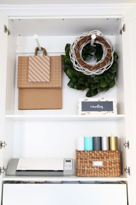 The IKEA PAX system was the perfect way to organize this messy corner of my office. I was able to store so much in the cabinets! | organized home office, office organization, IKEA hack, PAX wardrobe system, decor storage ideas, how to organize gift wrap, organized office supplies, wreath storage, gift bag storage, Silhouette cameo, wooden crates, vinyl rolls stored