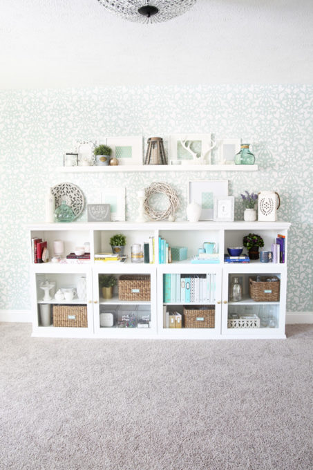 I love this IKEA BESTA hack to make a beautiful storage unit for a home office! And she tells you exactly how to do it too! | IKEA BESTA, IKEA hack, BESTA system, home office, DIY, trim work, office storage, office organization, organized office, shelf styling, bookshelf styling, styled shelves, functional and beautiful, attaching trim pieces to IKEA BESTA, crown molding, top trim pieces, styled bookcase from side view, How to Create Home Office Storage with the IKEA BESTA System featured