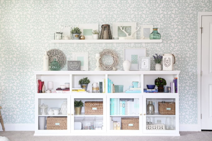 This extremely organized home office is so functional and beautiful at the same time! It gives me so many great ideas for my own home office organization! | home office, craft room, woman cave, home office decor, feminine decor, allover stencil, stenciled wall, IKEA BESTA system, IKEA PAX system, organizing, etagere, pillow organization, organized books, organized binders, organized office supplies, organized craft supplies, IKEA hack, office nook, home office storage, reading corner, Sherwin Williams Rainwashed, IKEA BESTA with custom trim work