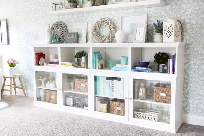This extremely organized home office is so functional and beautiful at the same time! It gives me so many great ideas for my own home office organization! | home office, craft room, woman cave, home office decor, feminine decor, allover stencil, stenciled wall, IKEA BESTA system, IKEA PAX system, organizing, etagere, pillow organization, organized books, organized binders, organized office supplies, organized craft supplies, IKEA hack, office nook, home office storage, reading corner, Sherwin Williams Rainwashed, IKEA BESTA with custom trim work, books organized by color