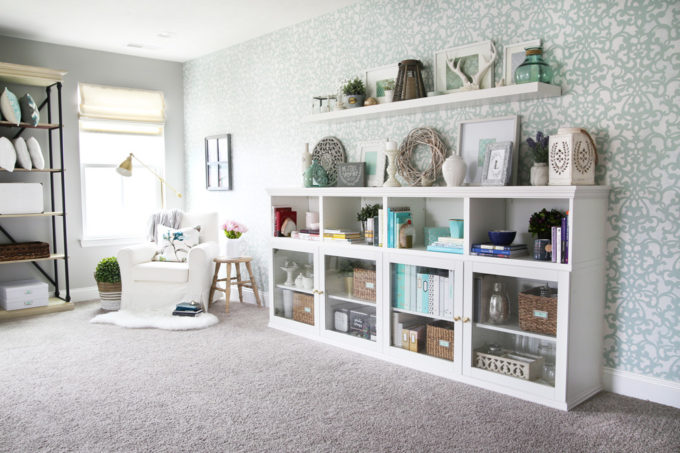 This extremely organized home office is so functional and beautiful at the same time! It gives me so many great ideas for my own home office organization!   home office, craft room, woman cave, home office decor, feminine decor, allover stencil, stenciled wall, IKEA BESTA system, IKEA PAX system, organizing, etagere, pillow organization, organized books, organized binders, organized office supplies, organized craft supplies, IKEA hack, office nook, home office storage, storage basket with adhesive bookplate label, IKEA LACK shelf, styled shelves, shelf styling