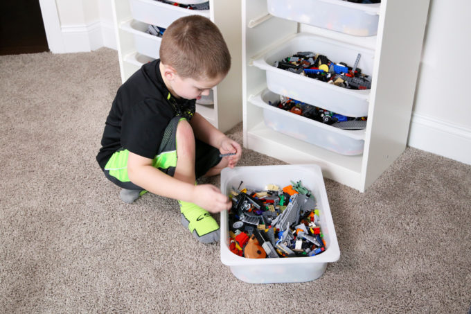LEGO organization can be a huge challenge, but I've figured out a few strategies to keep them neat and tidy (and help save your sanity)! | Organized LEGOs, how to organize LEGO, LEGO bins, LEGO sets, IKEA TROFAST storage unit, how to store LEGO pieces, LEGO organization system, LEGO organizing ideas, boy playing with LEGOs