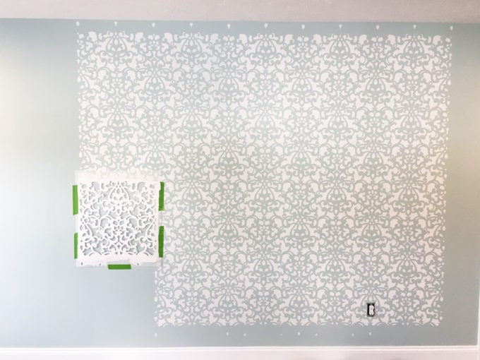 This detailed post is so helpful in teaching how to stencil a wall, allover stenciling! The outcome is absolutely gorgeous! | stenciled wall, stenciling, allover stencil, damask stencil, base color, Sherwin Williams Rainwashed, stenciling in progress, stencil taped on the wall with painter's tape
