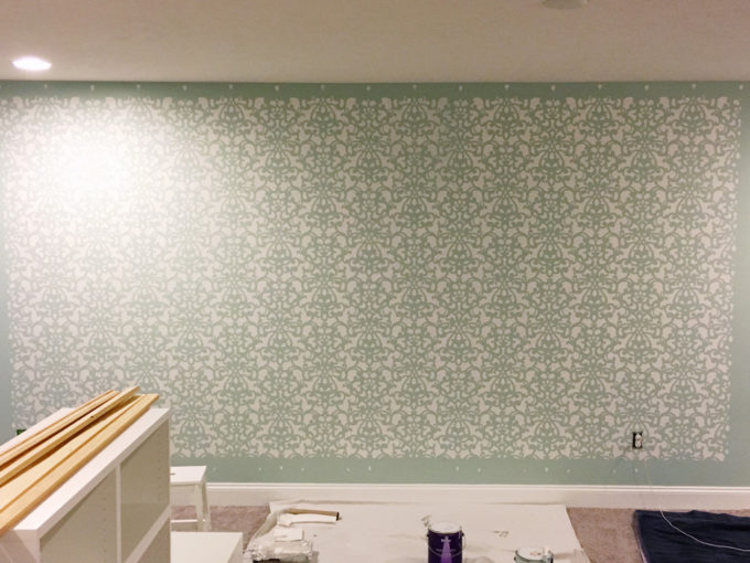 This detailed post is so helpful in teaching how to stencil a wall, allover stenciling! The outcome is absolutely gorgeous! | stenciled wall, stenciling, allover stencil, damask stencil, base color, Sherwin Williams Rainwashed, stenciling in progress, stenciled wall minus borders