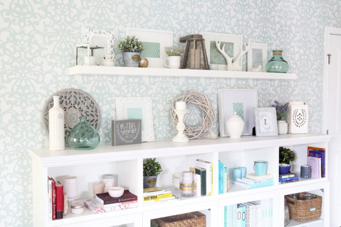 This extremely organized home office is so functional and beautiful at the same time! It gives me so many great ideas for my own home office organization!   home office, craft room, woman cave, home office decor, feminine decor, allover stencil, stenciled wall, IKEA BESTA system, IKEA PAX system, organizing, etagere, pillow organization, organized books, organized binders, organized office supplies, organized craft supplies, IKEA hack, office nook, home office storage, storage basket with adhesive bookplate label, IKEA LACK shelf, styled shelves