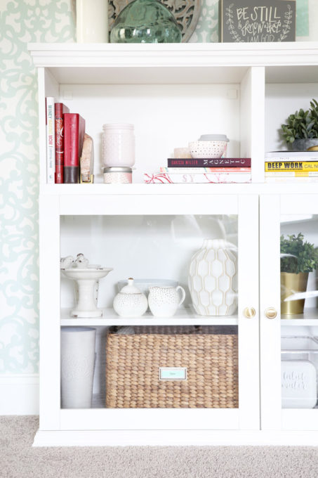 This extremely organized home office is so functional and beautiful at the same time! It gives me so many great ideas for my own home office organization!   home office, craft room, woman cave, home office decor, feminine decor, allover stencil, stenciled wall, IKEA BESTA system, IKEA PAX system, organizing, etagere, pillow organization, organized books, organized binders, organized office supplies, organized craft supplies, IKEA hack, office nook, home office storage, storage basket with adhesive bookplate label, glass front cabinet doors
