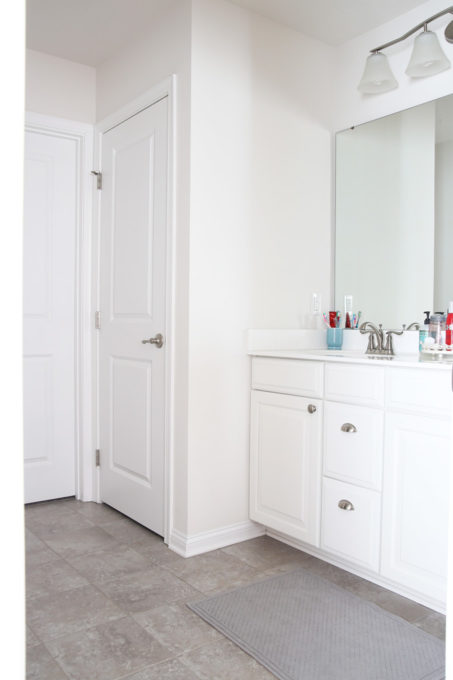 I'm sharing all of my favorite master bathroom organization ideas and some easy updates that we've done to take our master bathroom from cluttered and boring to organized and beautiful! | bathroom organization, organized bathroom vanity, how to organize a bathroom, how to organize deep vanity drawers, organized hair supplies, shaving tools organization, before photo of boring master bathroom