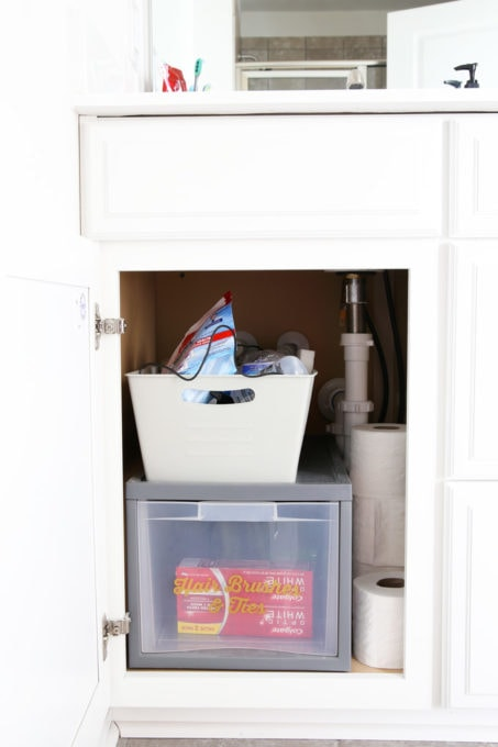 I'm sharing all of my favorite master bathroom organization ideas and some easy updates that we've done to take our master bathroom from cluttered and boring to organized and beautiful! | bathroom organization, organized bathroom vanity, how to organize a bathroom, how to organize deep vanity drawers, organized hair supplies, shaving tools organization, before photo of cluttered vanity cabinet