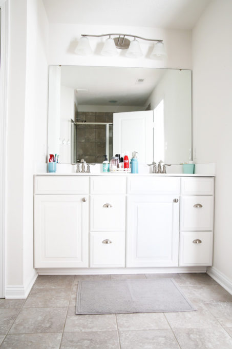 I'm sharing all of my favorite master bathroom organization ideas and some easy updates that we've done to take our master bathroom from cluttered and boring to organized and beautiful! | bathroom organization, organized bathroom vanity, how to organize a bathroom, how to organize deep vanity drawers, organized hair supplies, shaving tools organization, before photo