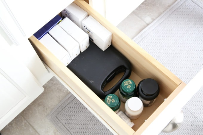 I'm sharing all of my favorite master bathroom organization ideas and some easy updates that we've done to take our master bathroom from cluttered and boring to organized and beautiful! | bathroom organization, organized bathroom vanity, how to organize a bathroom, how to organize deep vanity drawers, organized hair supplies, shaving tools organization, before photo of cluttered vanity drawer with toiletries