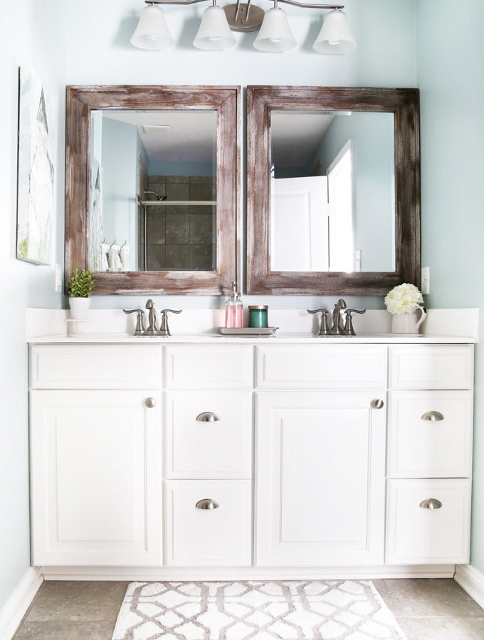 I'm sharing all of my favorite master bathroom organization ideas and some easy updates that we've done to take our master bathroom from cluttered and boring to organized and beautiful! | bathroom organization, organized bathroom vanity, how to organize a bathroom, how to organize deep vanity drawers, organized hair supplies, shaving tools organization, change out builder grade mirrors for wooden framed mirrors