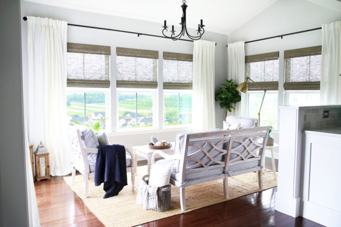 Sunroom with Whitewashed Wood Furniture, Woven Wood Shades, and White Curtains