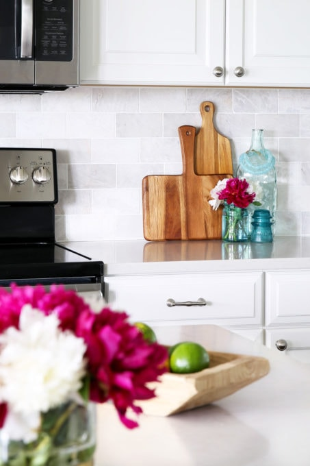 Cutting Boards Against Marble Subway Tile Backsplash with Pink Peonies, Summer Home Tour