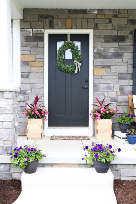 Stone Exterior, Black Front Door, Wooden Planters, Pink and Purple Flowers