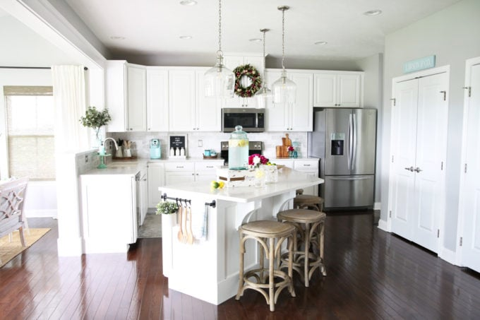 White Kitchen with Large Island, Dark Floors, and Clear Pendant Lights