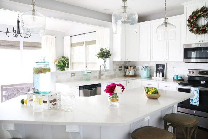 White Kitchen with Quartz Countertops and Clear Pendant Lights Over the Island