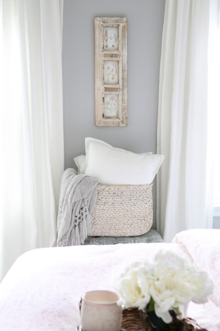 Woven Basket Holding Pillows and Blankets in a Guest Bedroom