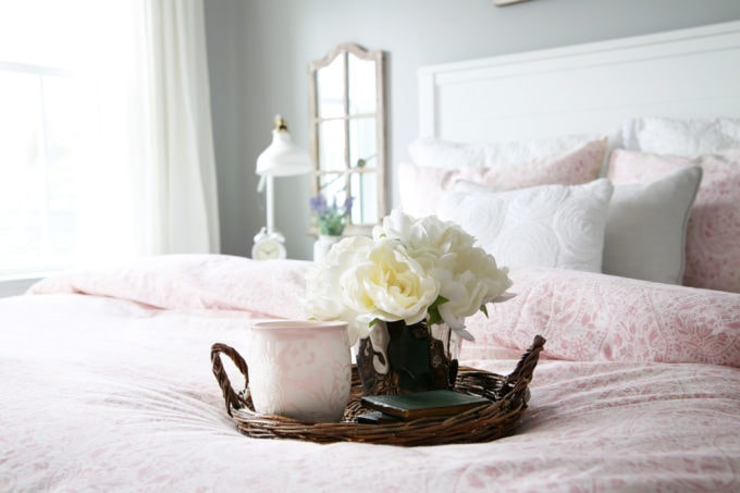 Wicker Tray with Candle and Faux Flowers on a Pink Duvet Cover in a Guest Bedroom