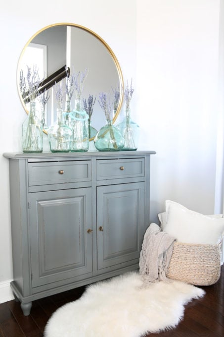 Entry Cabinet with Round Mirror and Blue Glass Jars with Lavender