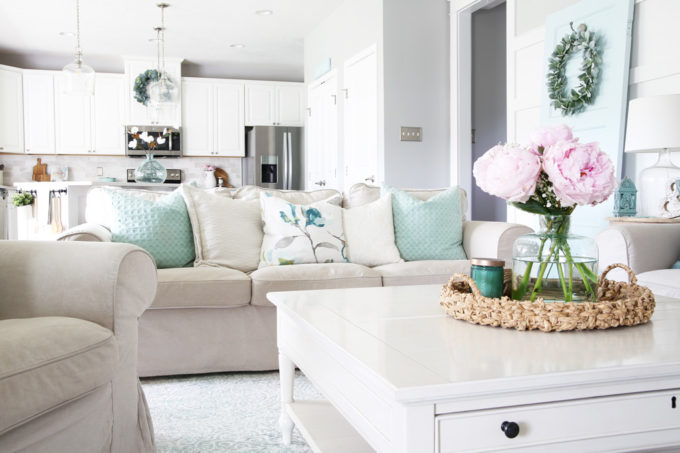 Flowers on Coffee Table, Couch with Pillows, White Kitchen