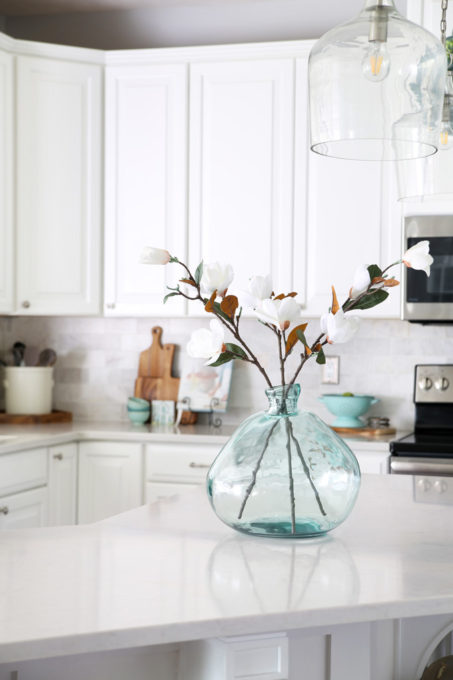 Aqua Demijohn on a Large Kitchen Island in a White Kitchen