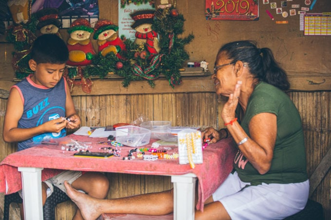 little boy and grandmother making beaded jewelry in Ecuador