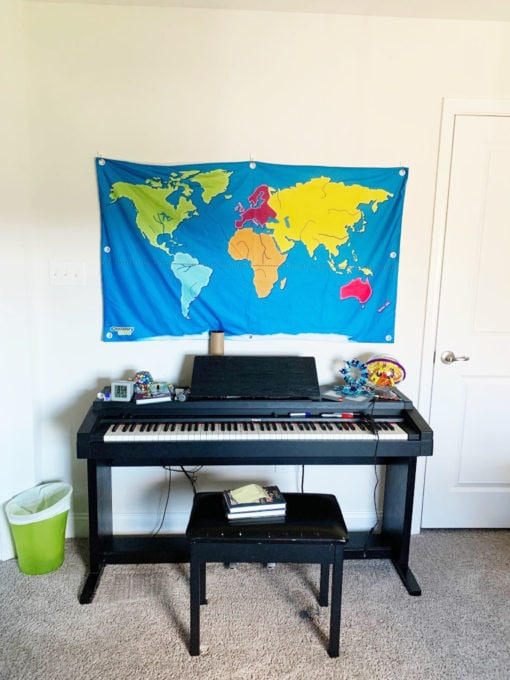 Cluttered Piano in Playroom Before Photo