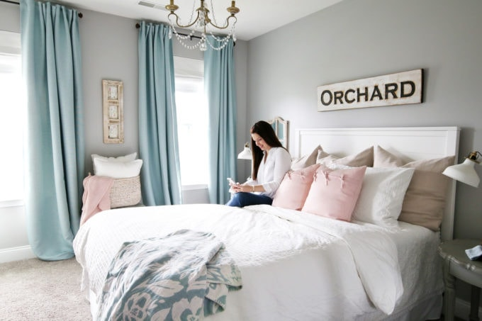 Woman Sitting on Bed in Beautiful Bedroom