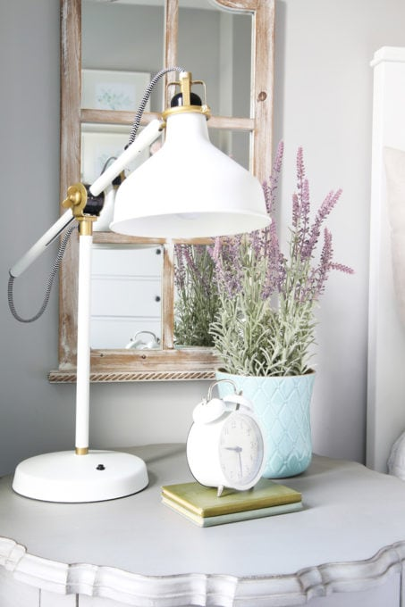 Nightstand with Clock, Faux Plant, and White Lamp