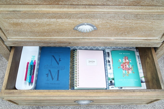 Organized Nightstand Drawer with Books, Notebooks, and Writing Utensils