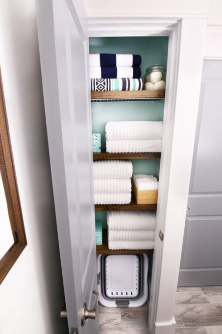 Organized Linen Closet with Wood Shelf Covers Over Wire Shelves