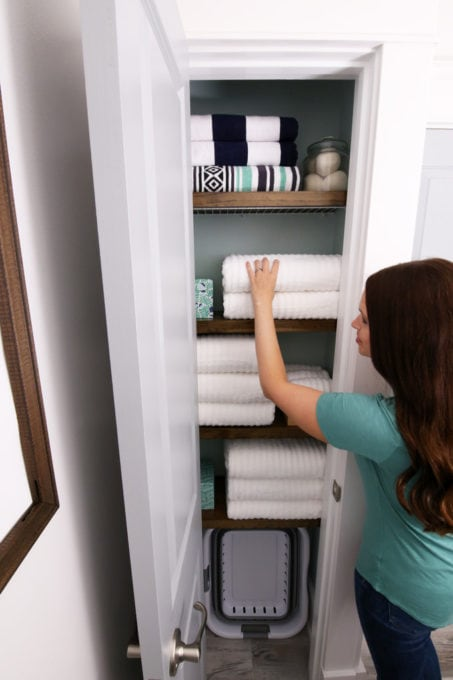 Woman Reaching for a Towel in an Organized Linen Closet
