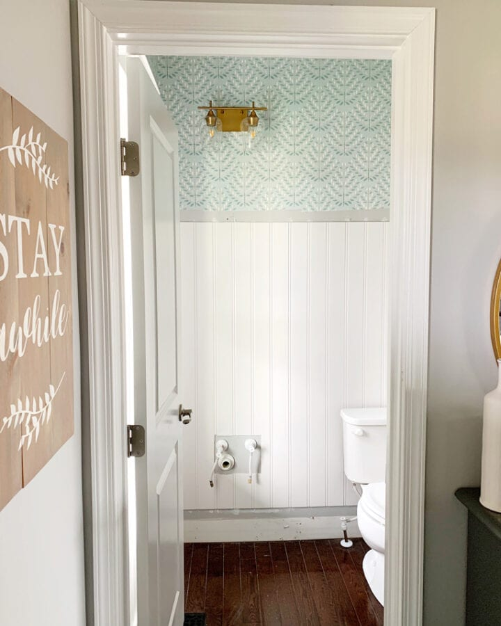 Powder Room with Beadboard and Wallpaper with Brass Light Fixture
