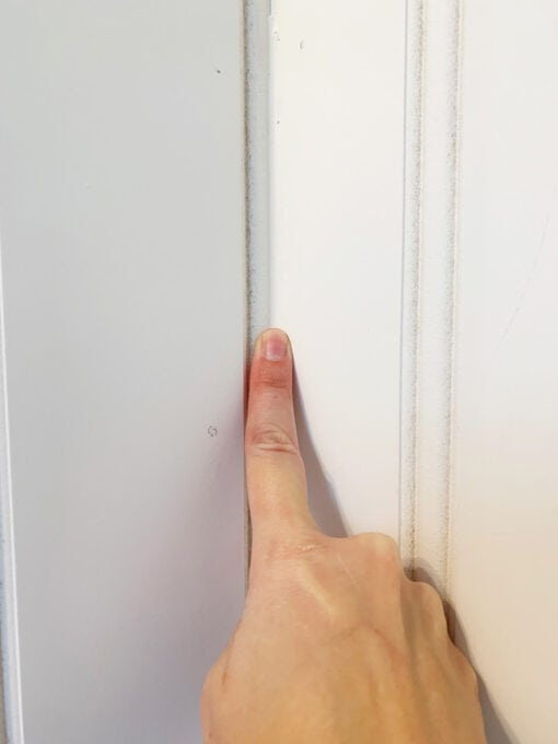 Smoothing Caulk with Finger on Beadboard Paneling in Half Bath