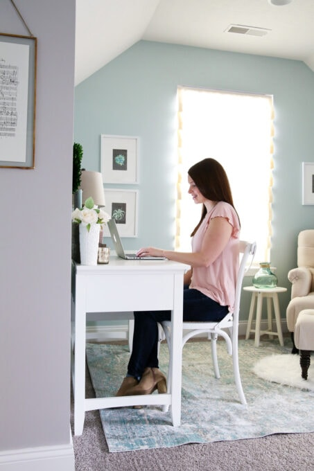 Woman in pink shirt sitting at a white desk, typing on a laptop computer