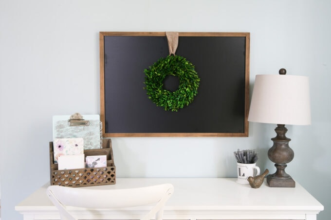 Desktop with Organizer, Lamp, and Mug of Pens. A Blackboard Hangs on the Wall with a Green Boxwood Wreath Over It.